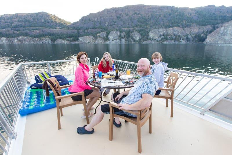 Gelukkige familie van vier die samen buiten bij een meer zitten die diner eten royalty-vrije stock afbeelding