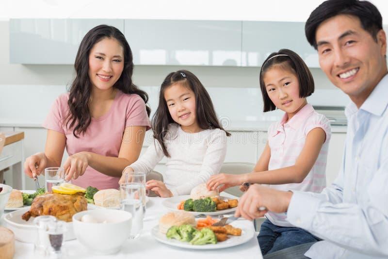 Gelukkige familie van vier die van gezonde maaltijd in keuken genieten stock foto's