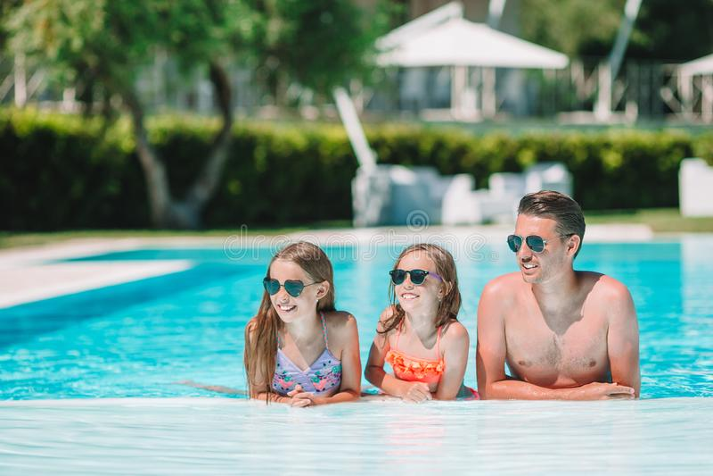 Gelukkige familie van vier in in openlucht zwembad stock afbeelding