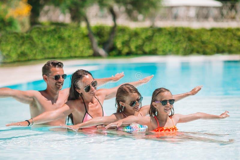 Gelukkige familie van vier in in openlucht zwembad stock foto's