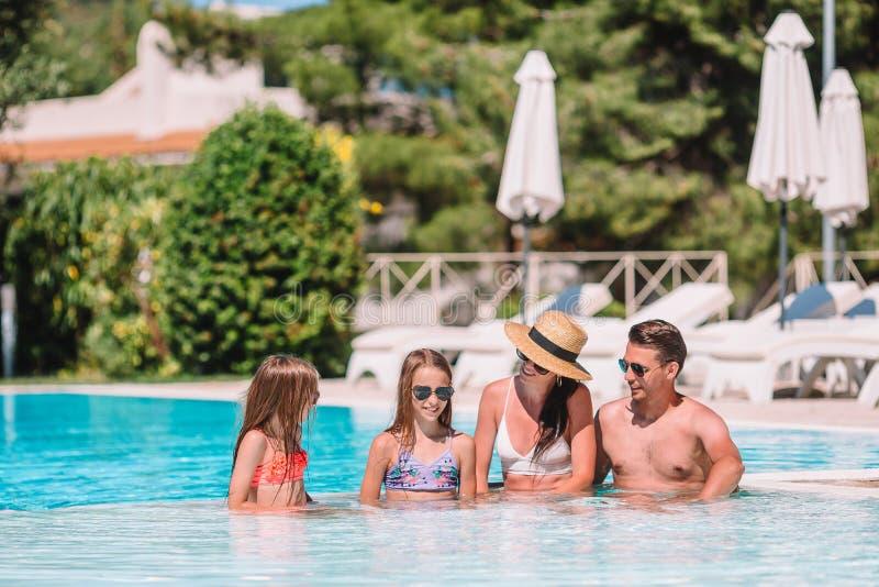 Gelukkige familie van vier in in openlucht zwembad royalty-vrije stock foto's