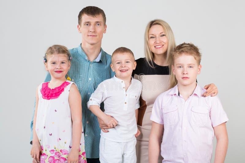 Gelukkige familie van vijf mensen, moeder die zoon koesteren stock foto
