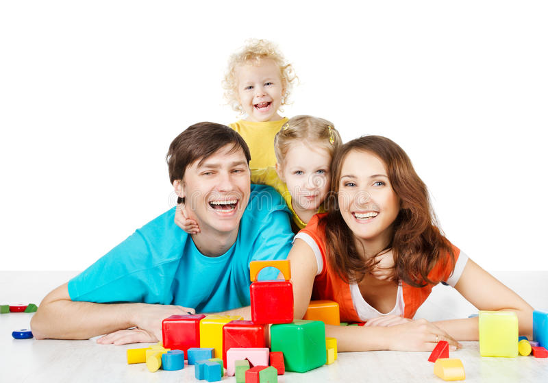 Gelukkige familie vier personen. Het glimlachen van oudersjonge geitjes die speelgoedblo spelen stock afbeeldingen