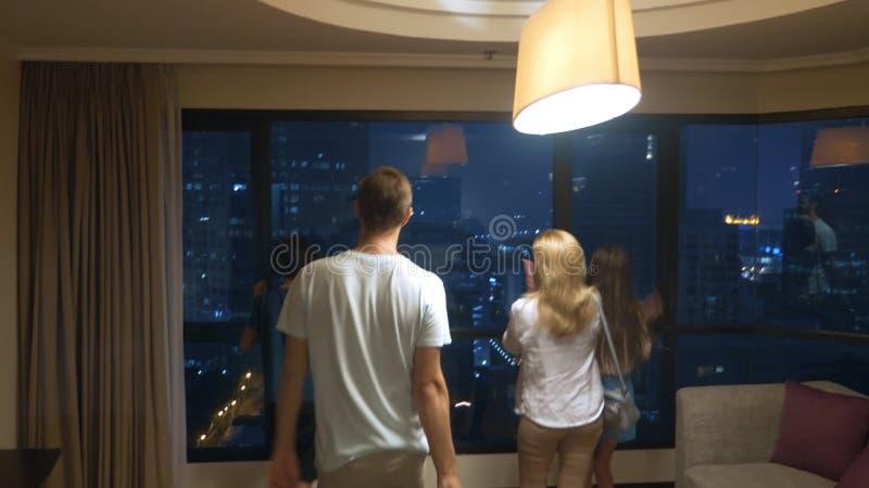Gelukkige familie, vrouw, man op de achtergrond van wolkenkrabbers in het panoramische venster in de avond royalty-vrije stock fotografie