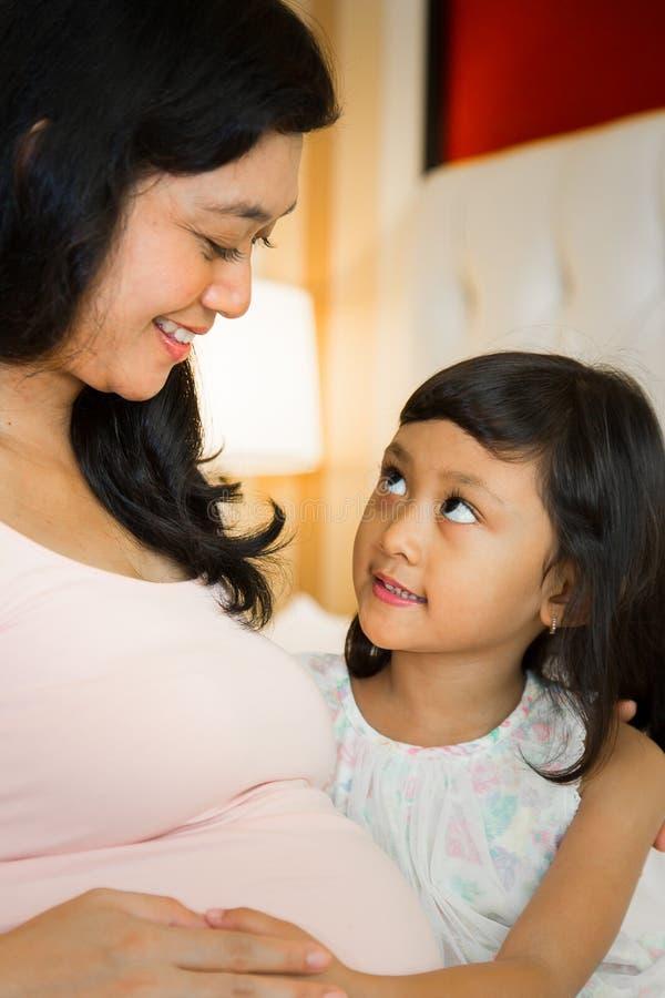 Gelukkige familie zwangere moeder en dochter stock fotografie