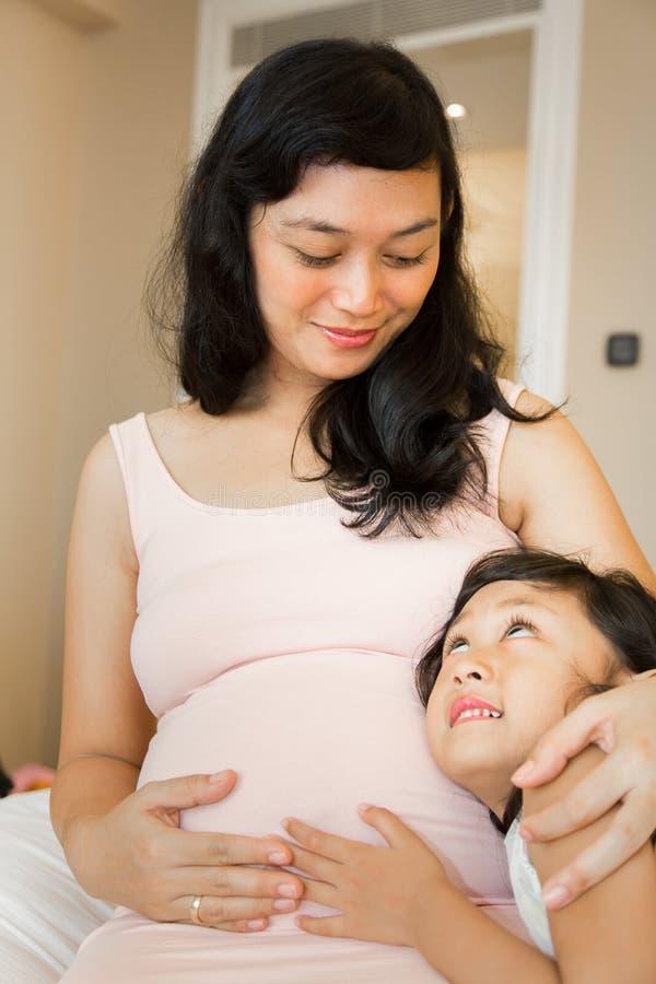 Gelukkige familie zwangere moeder en dochter stock foto's