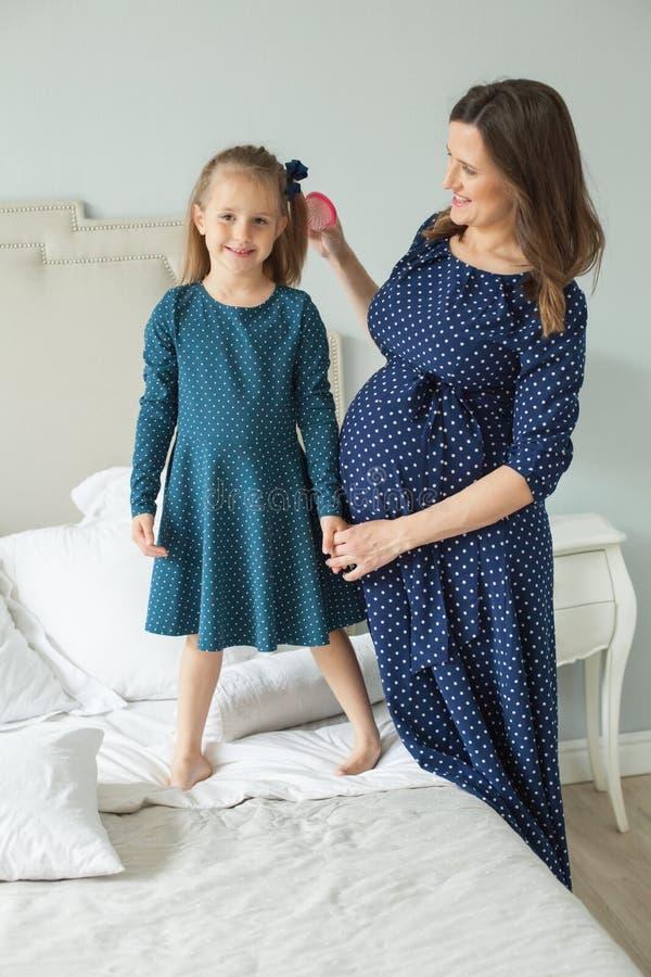 Gelukkige Familie Zwangere moeder en weinig dochter stock foto's