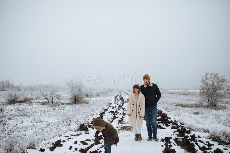 Gelukkige familiegang op de sneeuwweg Mamma, papa, dochtertribune in openlucht op de achtergrondwinter stock afbeelding