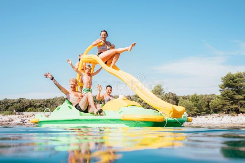 Gelukkige familiehanden omhoog op de drijvende Catamaran van de Speelplaatsdia aangezien zij die van de overzeese van de vakantie stock foto's