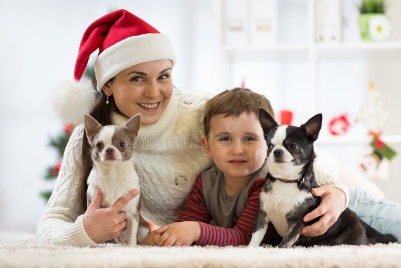 Gelukkige familieKerstmis Moeder, kindzoon en honden die de wintervakantie thuis vieren stock fotografie