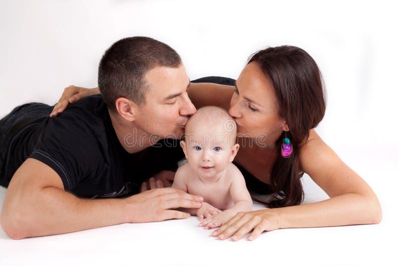Gelukkige familiekus - moeder, vader en baby stock afbeeldingen