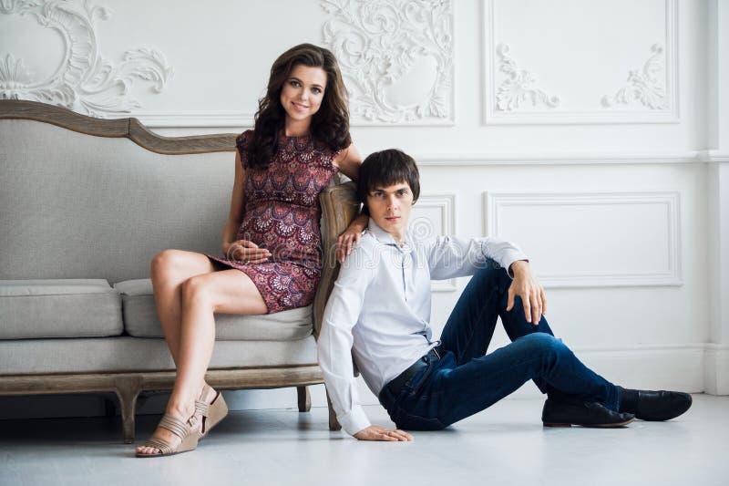 Gelukkige familielevensstijl Het jonge paar verwacht een baby Zwangere vrouwenzitting op bank en het kijken aan camera met haar royalty-vrije stock fotografie