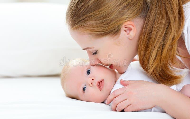 Gelukkige familiemoeder die haar pasgeboren baby kussen royalty-vrije stock fotografie