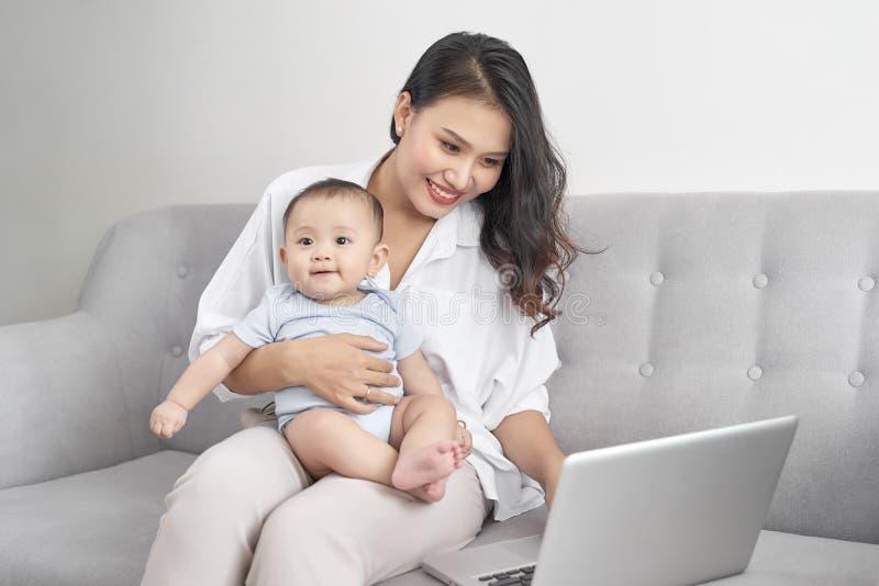 Gelukkige familiemoeder en baby die thuis laptop computer met behulp van royalty-vrije stock foto