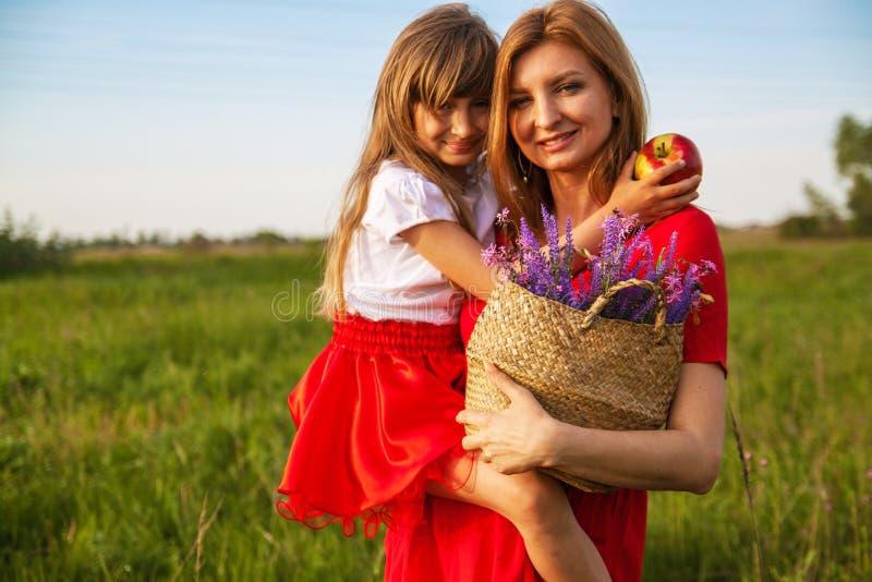 Gelukkige familiemoeder en dochter die in de zomer op de aard koesteren stock foto's