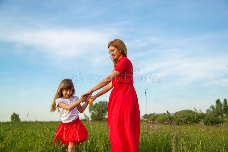 Gelukkige familiemoeder en dochter die in de zomer op de aard koesteren royalty-vrije stock foto