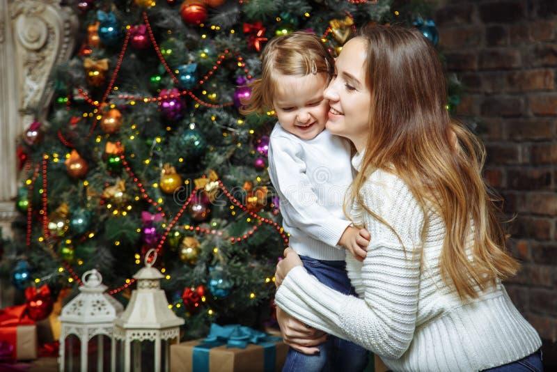 Gelukkige familiemoeder en dochter die dichtbij Kerstboom koesteren stock foto's
