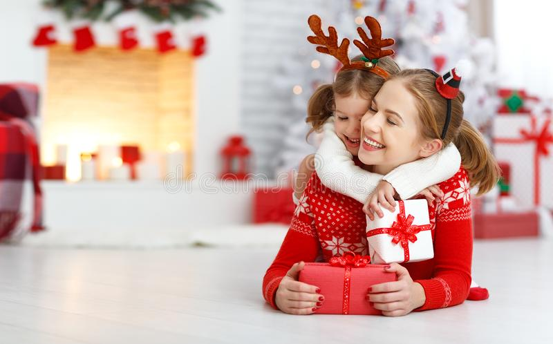 Gelukkige familiemoeder en dochter die Kerstmisgift geven stock foto's