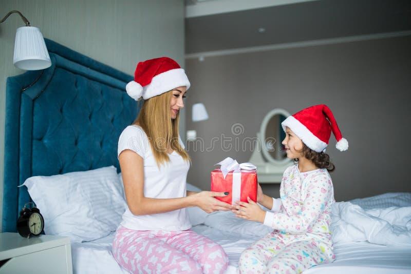 Gelukkige familiemoeder en kinddochter die giften in bed op Kerstmisochtend geven stock foto