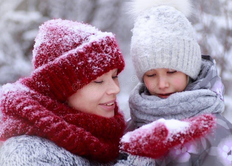 Gelukkige familiemoeder en kinddochter die pret hebben, die bij de wintergang in openlucht spelen royalty-vrije stock afbeeldingen