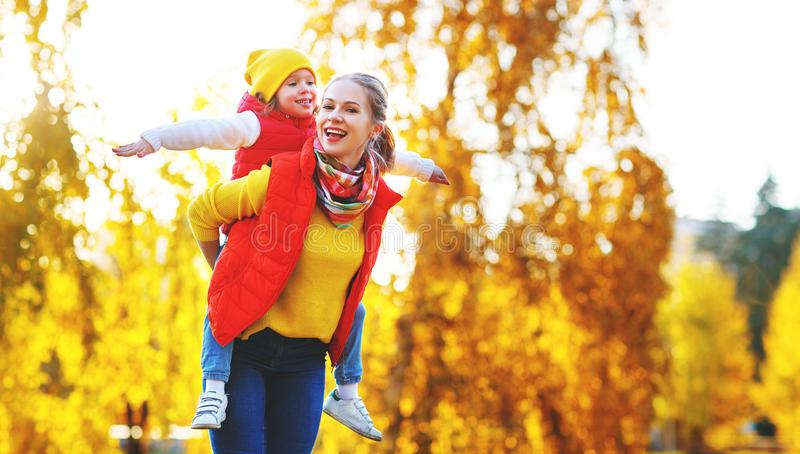 Gelukkige familiemoeder en kinddochter op de herfstgang royalty-vrije stock afbeelding