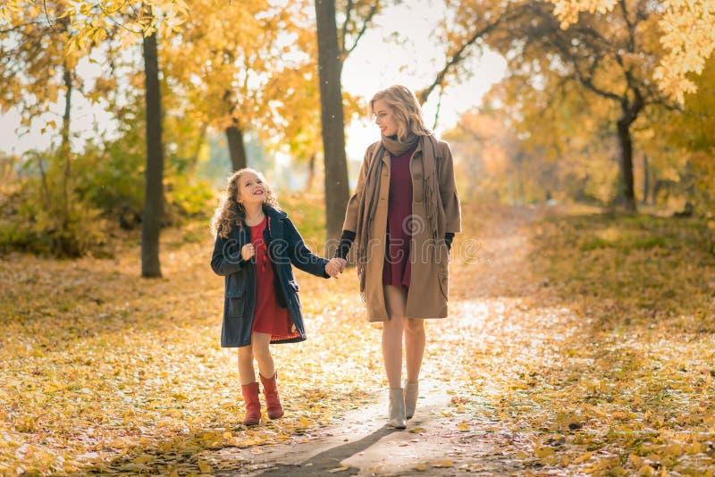 Gelukkige familiemoeder en kinddochter op de herfstgang royalty-vrije stock foto