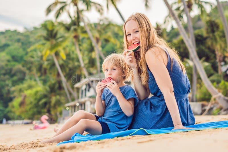 Gelukkige familiemoeder en zoon die een watermeloen op het strand eten De kinderen eten gezond voedsel stock fotografie
