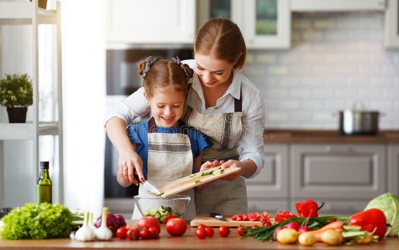 Gelukkige familiemoeder met kindmeisje die plantaardige salade voorbereiden stock foto's