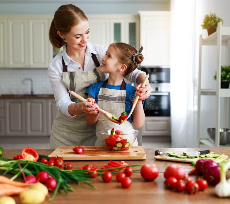 Gelukkige familiemoeder met kindmeisje die plantaardige salade voorbereiden stock afbeelding