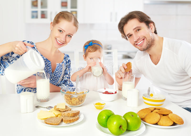 Gelukkige familiemoeder, vader die, de dochter van de kindbaby ontbijt hebben stock foto