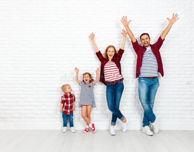 Gelukkige familiemoeder, vader, zoon, dochter op een witte blinde muur stock foto's