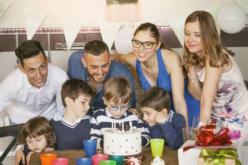 Gelukkige families met kinderen die rond een cake voor een verjaardag vieren royalty-vrije stock fotografie