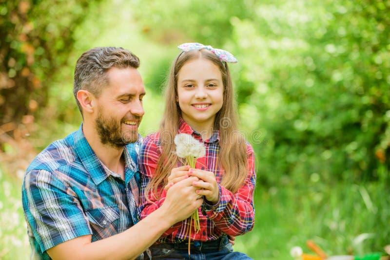 Gelukkige familievakantie De vader en het meisje genieten van zomer Papa en dochter die paardebloembloemen verzamelen houd stock afbeelding