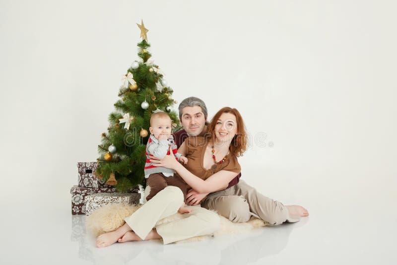 Gelukkige familiezitting bij de nieuw-jaarboom op witte studio royalty-vrije stock foto's