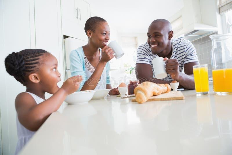 Gelukkige familiezitting en het nemen van ontbijt stock afbeeldingen
