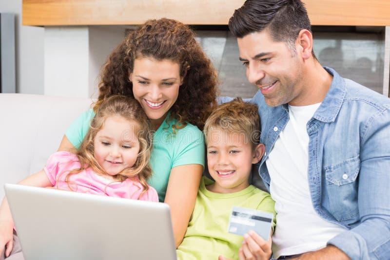 Gelukkige familiezitting op bank die laptop met behulp van samen om online te winkelen royalty-vrije stock afbeeldingen