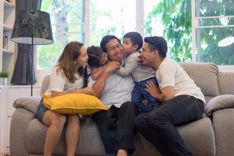 gelukkige familiezitting op bank die samen in woonkamer thuis spreken Multigeneratie kleinkinderen die grootvader kussen stock foto