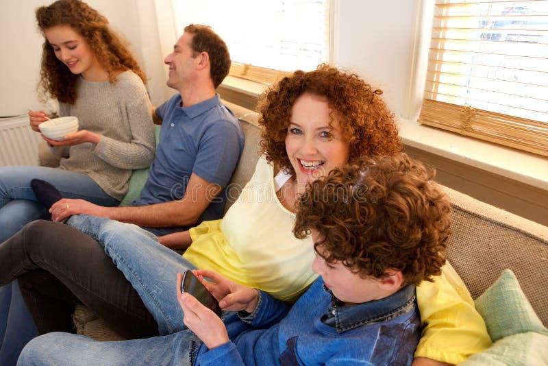 Gelukkige familiezitting op bank die tim samen van genieten stock foto