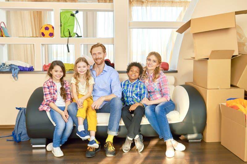 Gelukkige familiezitting op laag stock afbeelding