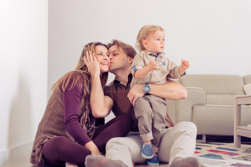 Gelukkige familiezitting op vloer met hun kleine baby Familie het besteden tijd thuis met hun zoon Vader die een moeder kussen stock afbeelding