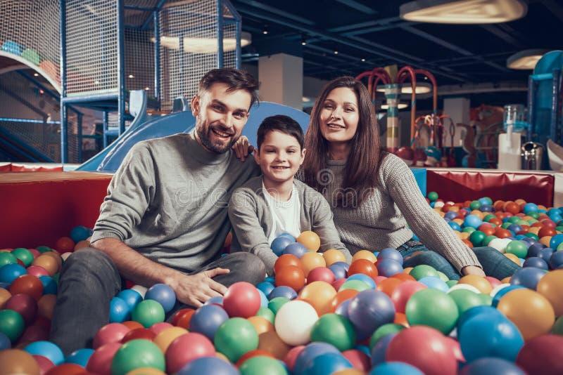 Gelukkige familiezitting in pool met ballen royalty-vrije stock afbeelding