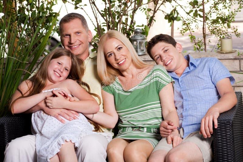 Gelukkige familiezitting in terras en het bekijken u royalty-vrije stock afbeeldingen