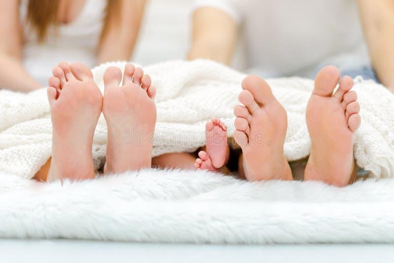 Gelukkige familiy in bed Van de moedervader en Baby Voeten onder Deken Boomparen benen royalty-vrije stock fotografie