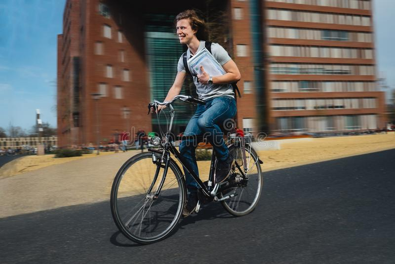 Gelukkige fietsboodschapper in een stormloop stock foto