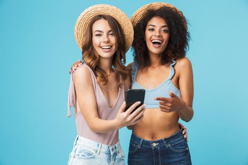 Gelukkige foto van twee het multi-etnische lachen en pointin van de zomermeisjes stock foto's