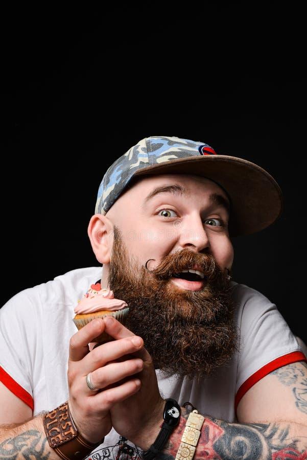 Gelukkige gebaarde kale mens die een roomcake met anticiperen van het genoegen van het eten houden royalty-vrije stock afbeelding