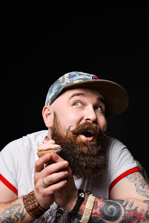 Gelukkige gebaarde kale mens die een roomcake met anticiperen van het genoegen van het eten houden royalty-vrije stock fotografie