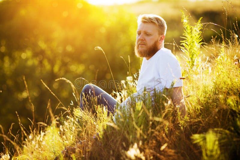 Gelukkige gebaarde kerel die onder wildflowers rusten royalty-vrije stock afbeelding