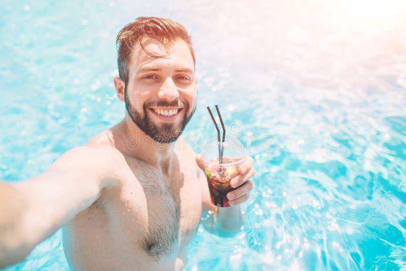 Gelukkige gebaarde mens die selfie in zwembad maken Hij drinkt een cocktail en het ontspannen stock foto