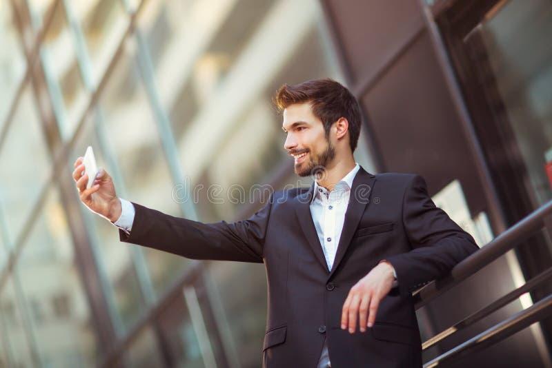 Gelukkige gebaarde zakenman die zich buiten de bureaubouw bevinden stock afbeelding